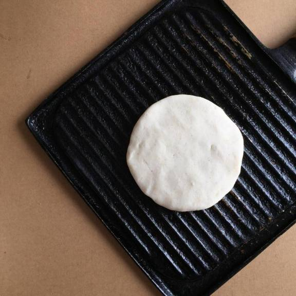 Lightly oil a large iron or grill pan over medium heat. Let the skillet get hot before adding the arepa dough. In batches, add the formed arepas disks to the skillet. Cook each arepa about 4-6 minutes on each side, or until they start to get light brown spots.