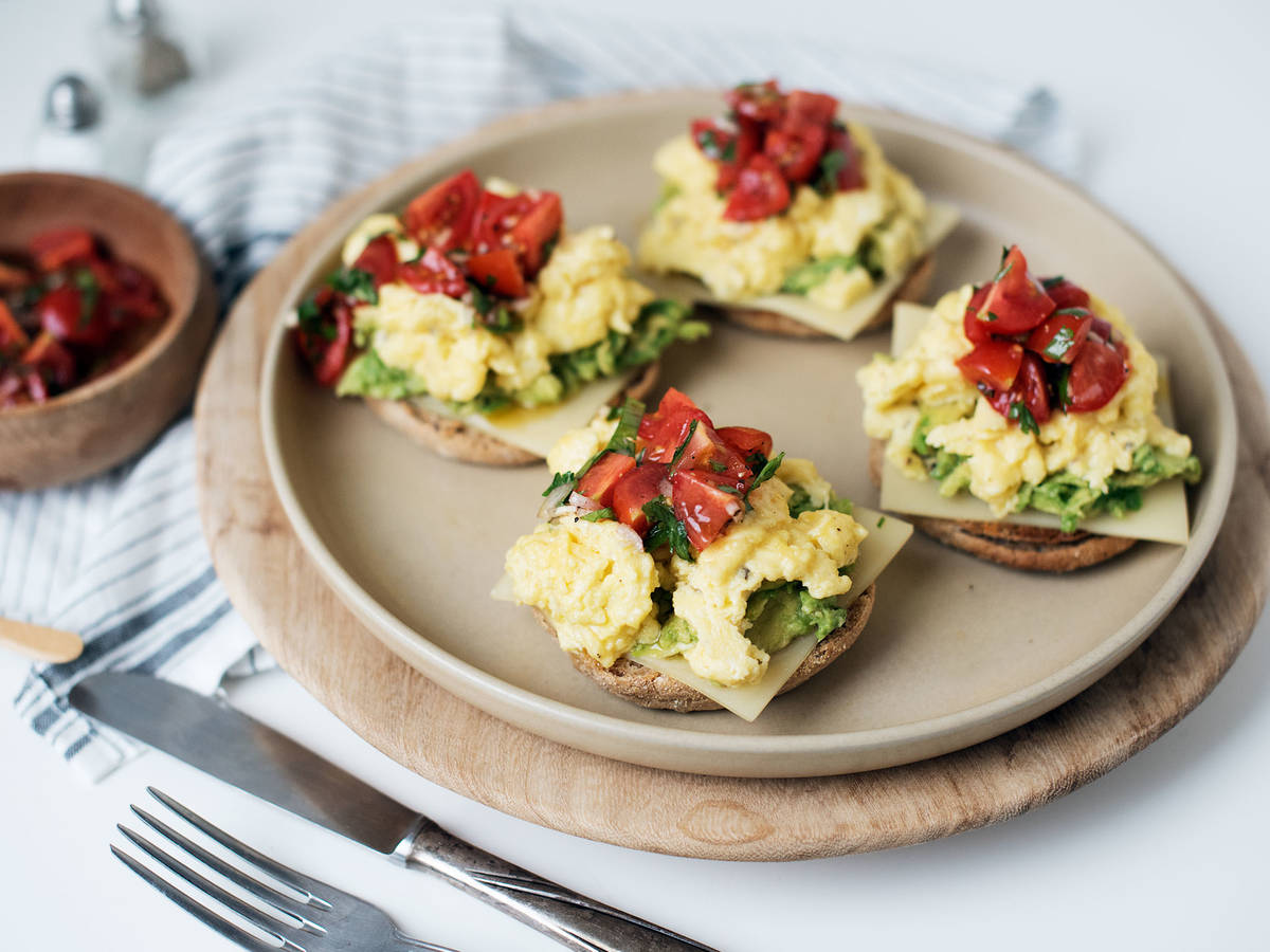 Scrambled eggs on avocado toast with salsa