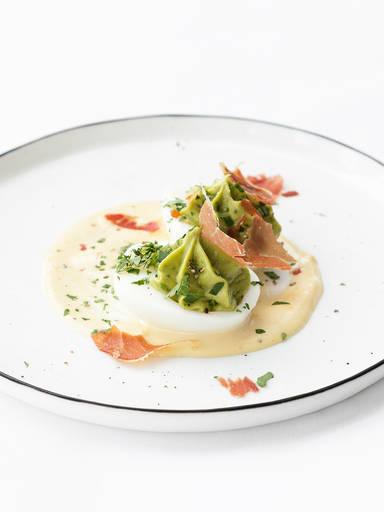 Deviled eggs with avocado cream and prosciutto