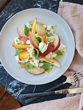 Peach Caprese salad with basil oil