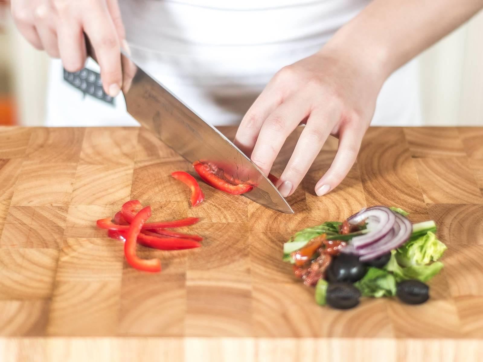 Nun Römersalatkopf waschen, trocknen und in mundgerechte Stücke portionieren. Salatgurke würfeln und schwarze Oliven halbieren. Rote Zwiebel, getrocknete Tomaten und Paprika in feine Streifen schneiden.