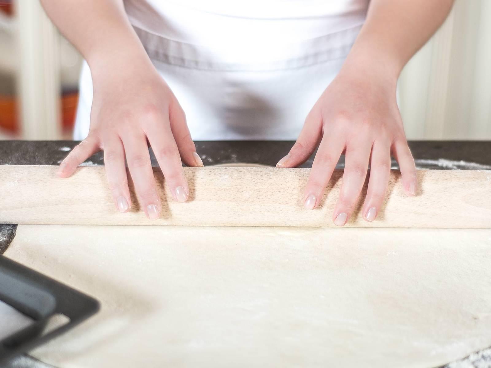 将烤箱预热至180摄氏度。将面团擀成约0,5厘米厚的面饼,放入铺有烘焙纸的烤盘中。