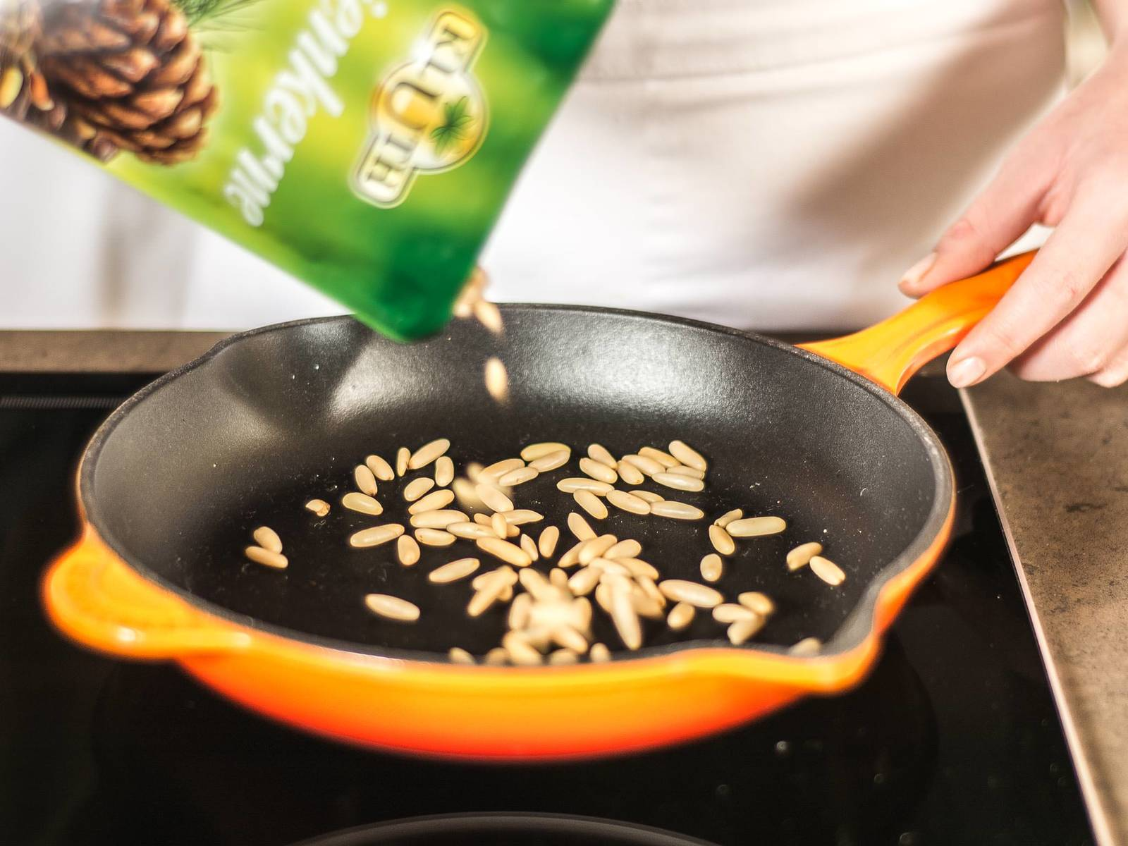 In the meantime, roast pine nuts in a small frying pan until brown, then finely chop them.