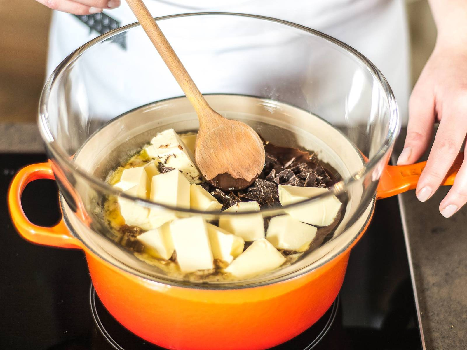 Preheat the oven to 190°C/ 375°F. Cut the  chocolate and butter into small pieces and slowly melt in a double boiler (water bath) with the sugar.