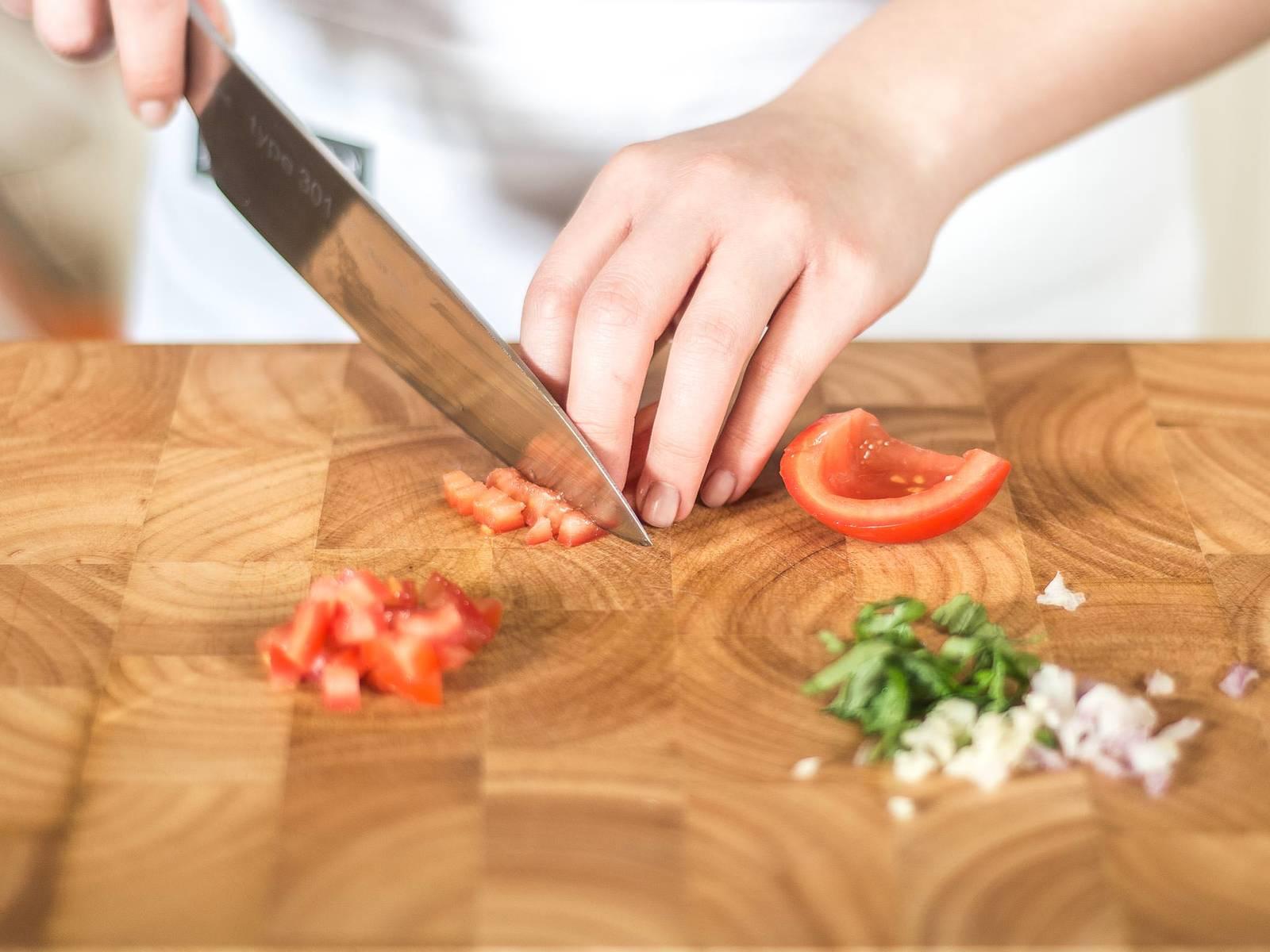 制作蒜香面包小点心:将蒜与小红洋葱切成小粒,罗勒叶切成细丝,西红柿先切成四半,去籽后再切成小粒。