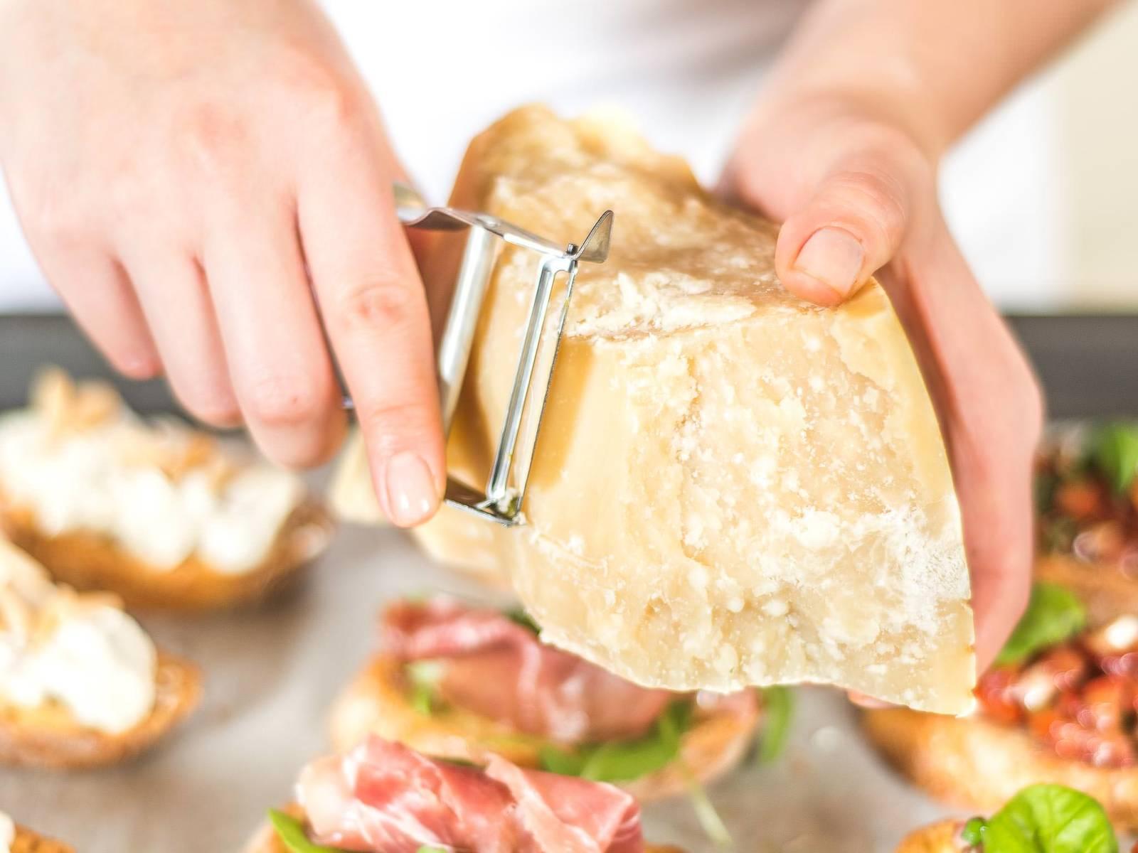 制作帕尔玛火腿面包小点心:将芝麻菜,火腿铺在最后1/3份的面包片上,然后将帕米森干酪擦碎,铺在火腿上即可。