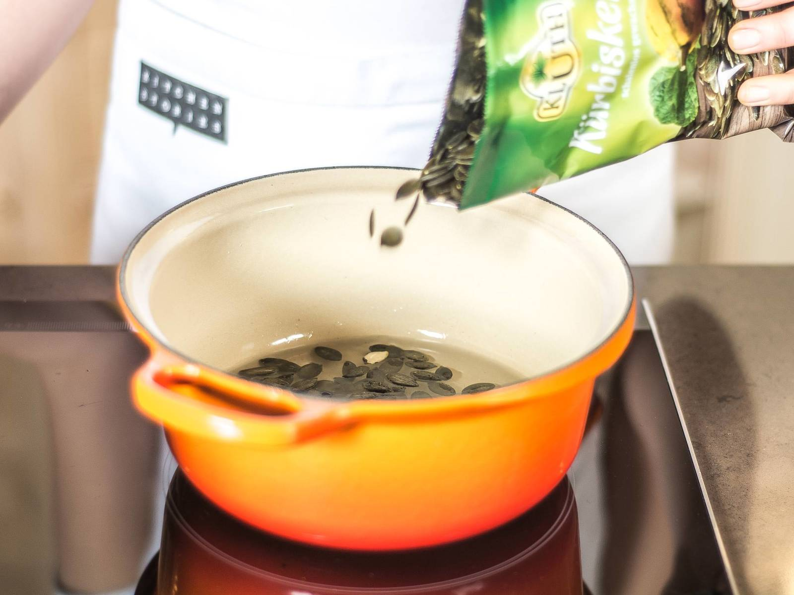 Place pumpkin seeds, water, and sugar in a small saucepan. While stirring constantly, heat until the water has fully evaporated and the sugar has caramelized and is amber-colored. The pumpkin seeds should rise slightly in the middle.
