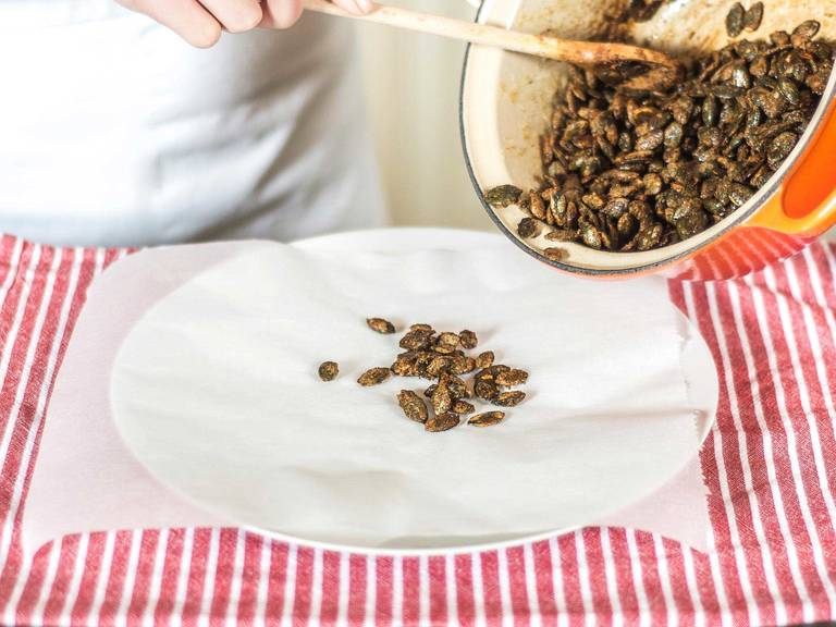 Place the candied pumpkin seeds on a sheet of parchment paper to cool.