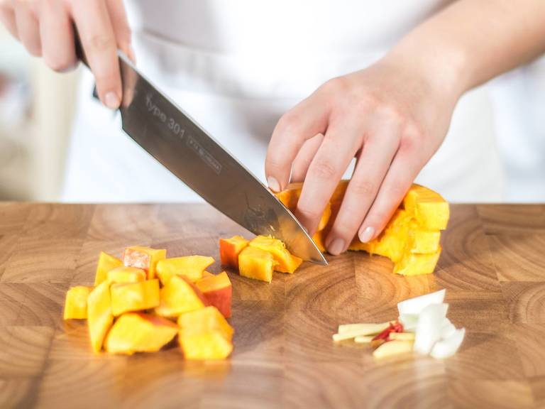 Cut onion into cubes and finely chop ginger and chili. If you wish to make the dish milder, remove the seeds from the chili. Halve the pumpkin, remove the seeds with a spoon, and cut the flesh of the pumpkin into cubes.