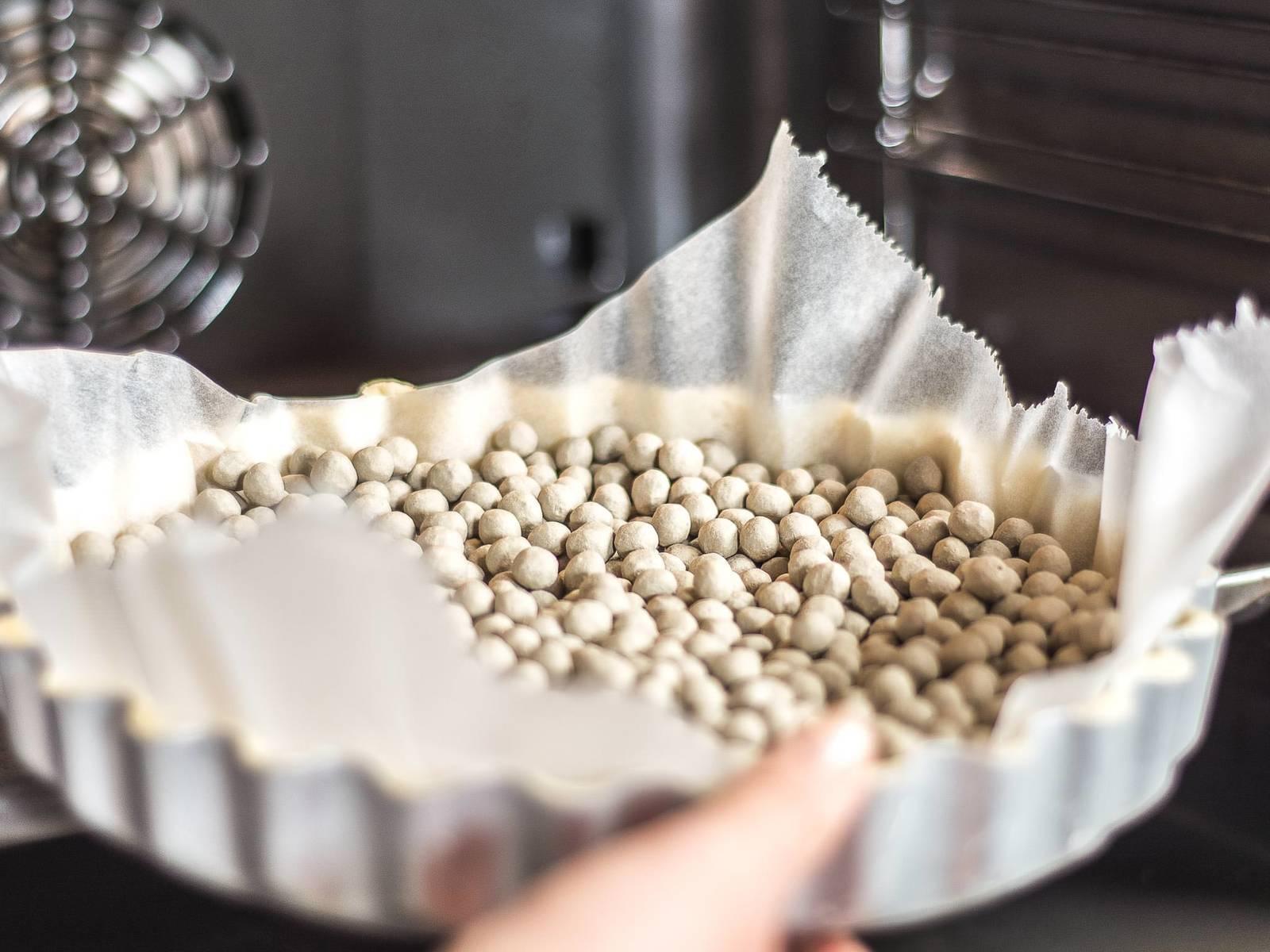 将面团擀成约0.3厘米厚的面皮,放入蛋糕烤盘中。在面皮上铺烘焙纸,再将干豌豆压在烘焙纸上,放入预热好的烤箱里,用180摄氏度盲烘烤12-15 分钟。从烤箱中取出后冷却10-15分钟。