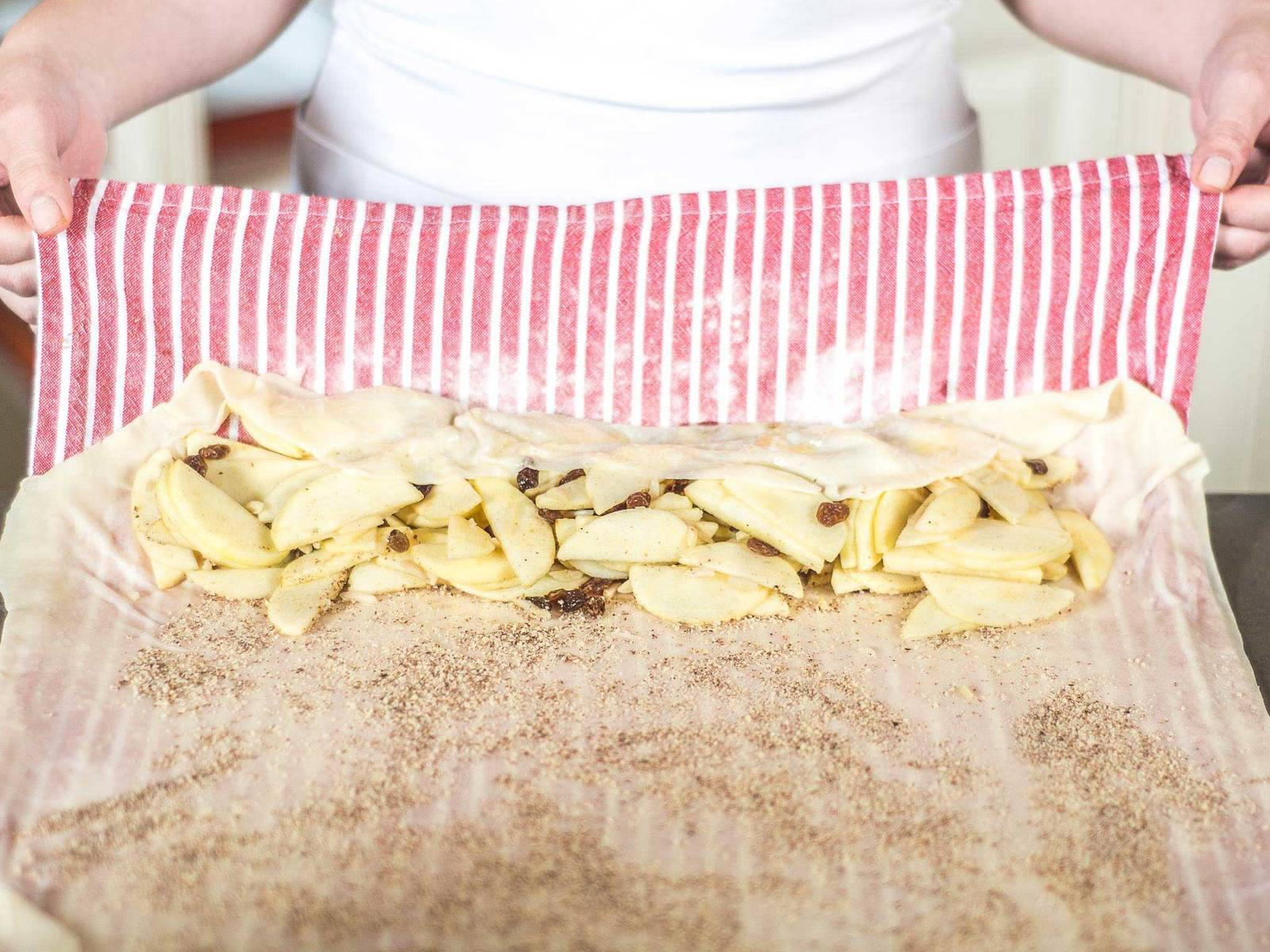 Using the kitchen towel, carefully fold the dough around the apple mixture.