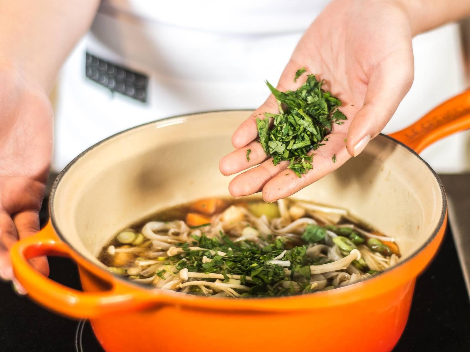 Nun die Reisnudeln abgießen und mit Frühlingszwiebeln, Enoki-Pilzen und Koriander zur Suppe hinzugeben. Direkt im Anschluss servieren, sodass die Pilze ihren Biss behalten und der Koriander seine Farbe.