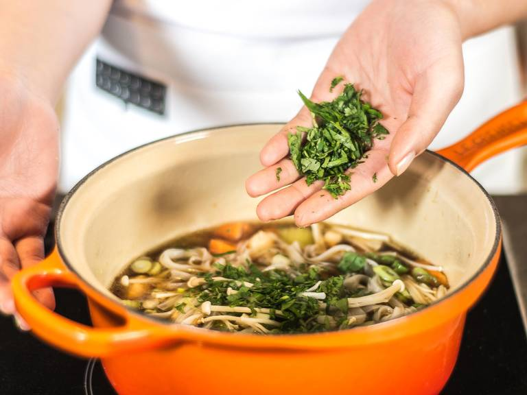Drain rice noodles and add to the soup, along with the green onions, enoki mushrooms, and cilantro. Serve immediately, so that the mushrooms keep their bite and the cilantro keeps its color.