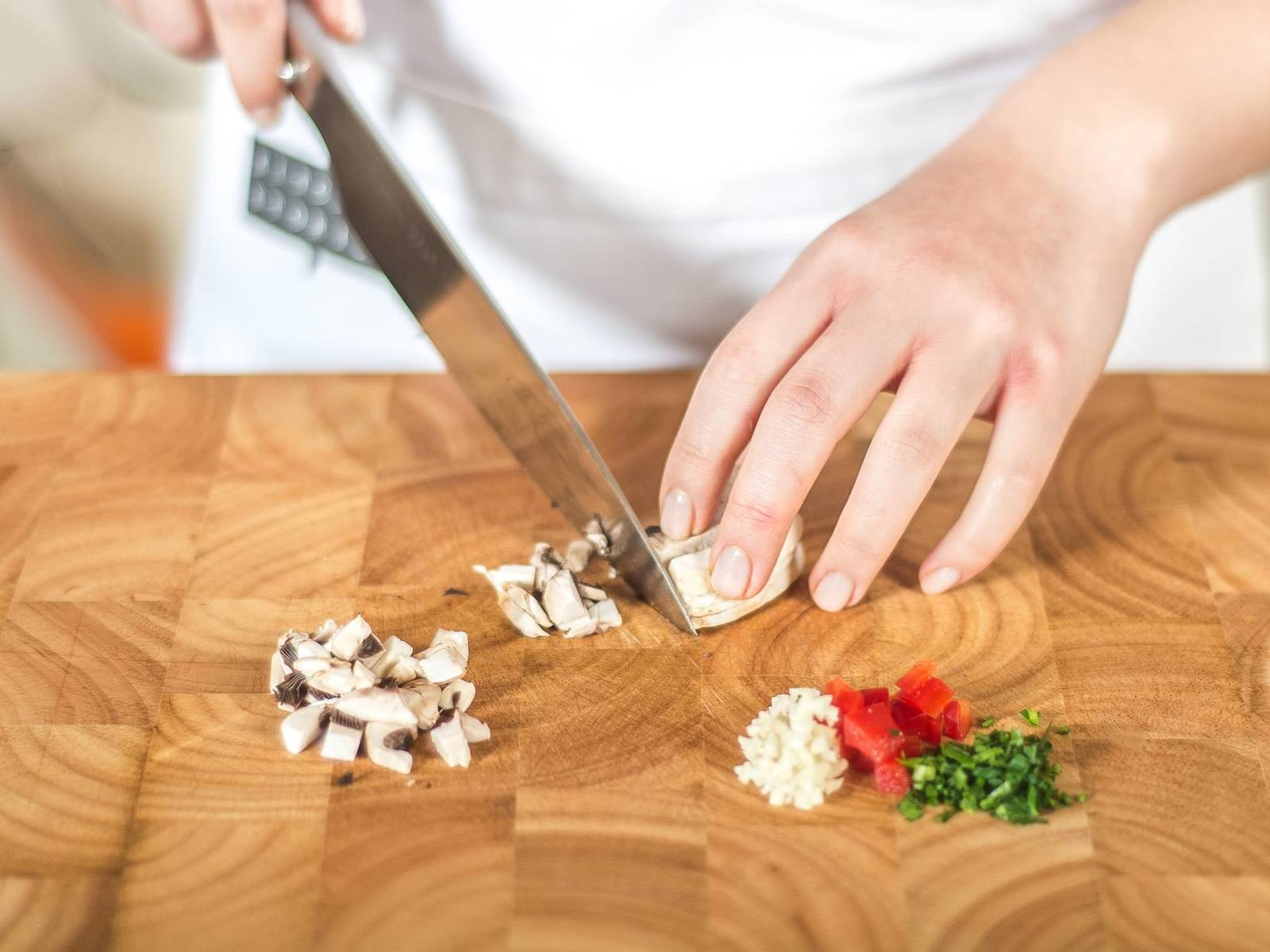 烤箱预热至180摄氏度。将欧芹与蒜切碎,灯笼椒与蘑菇切丁.