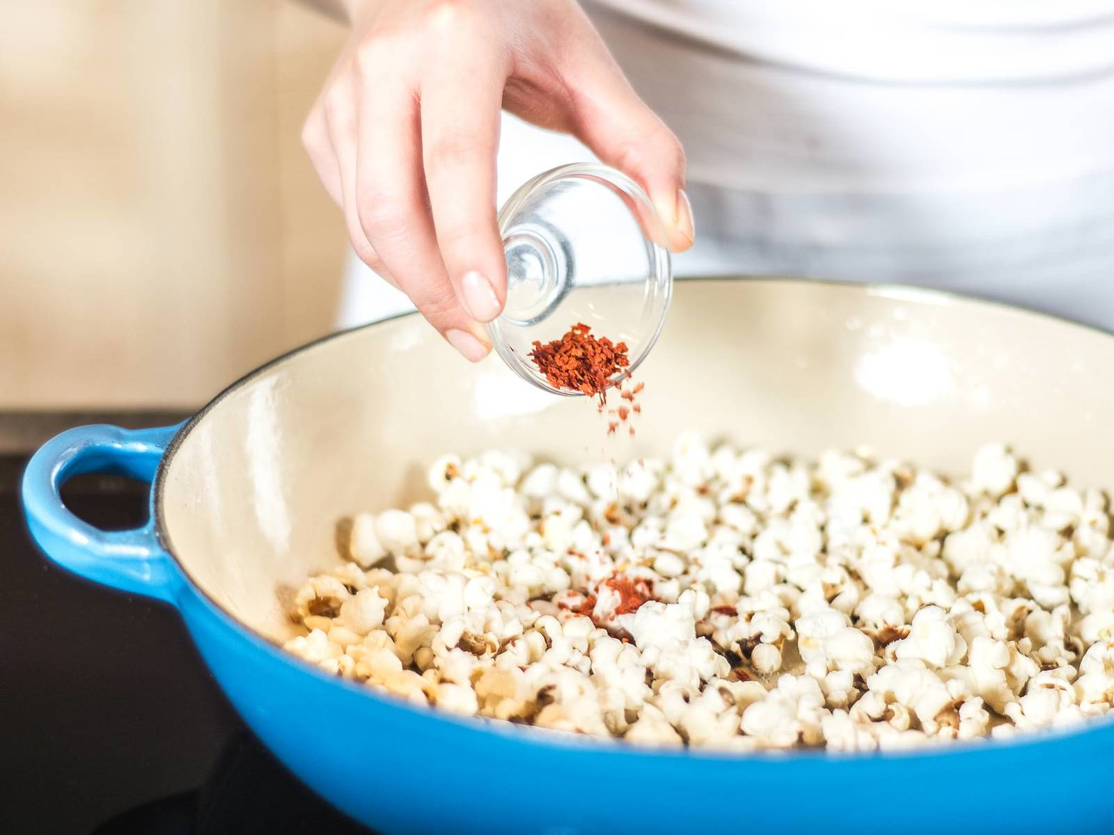To make the spicy popcorn, heat vegetable oil, then add popping corn and allow to pop on medium heat with a closed lid. When finished, season the popcorn as desired with chili powder and salt.