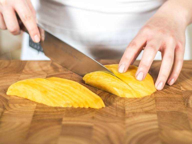 Now, peel the mango and carefully cut the flesh from the stone. Next, slice the two large sides of the fruit into fine strips.