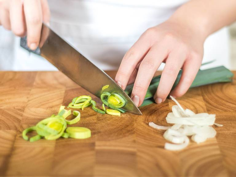 洋葱先切半,然后再切成细圈。将葱切也切细圈。