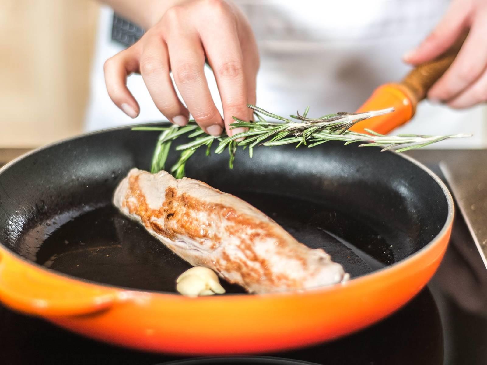 向猪里脊撒少许盐,在热锅中用高温煎至各面焦黄。然后加入胡椒粉,按碎的蒜瓣及迷迭香,再放入预热好的烤箱中用180摄氏度烤约10分钟。