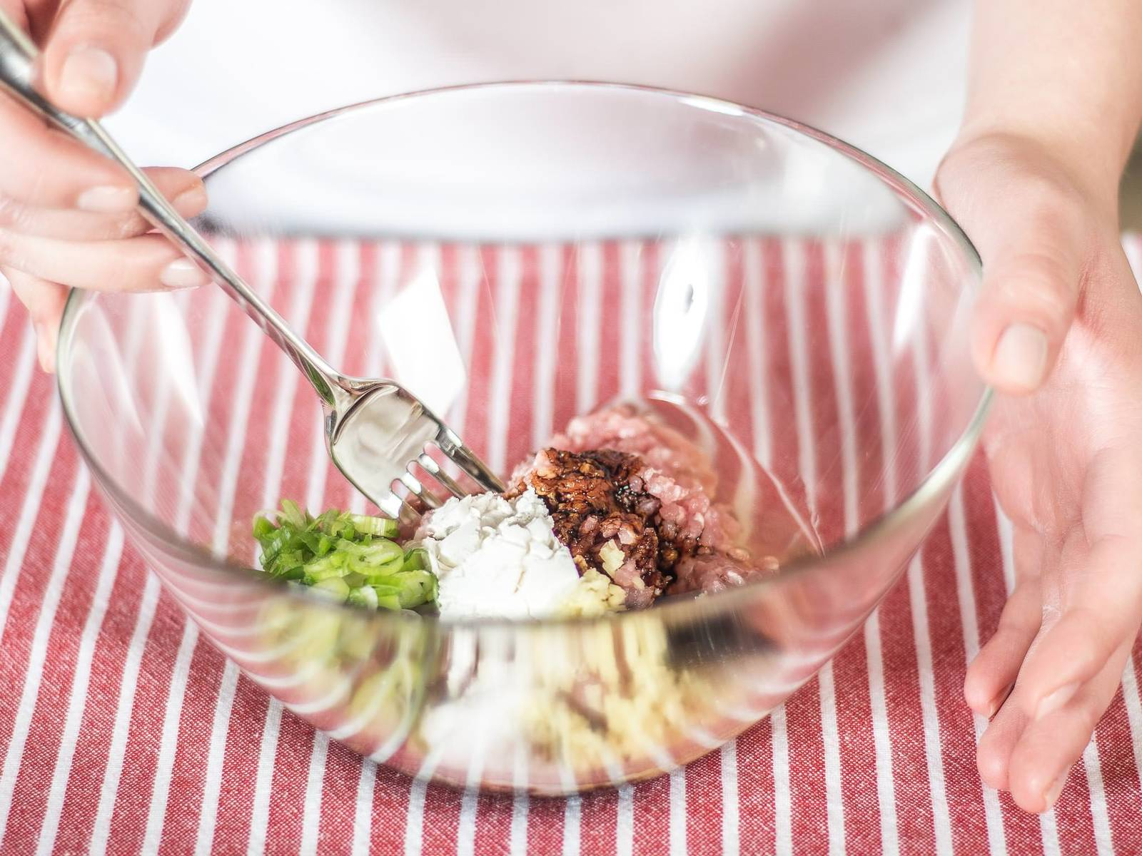 Mix ground meat, chopped spring onion, chopped ginger, egg white, cornstarch, soy sauce, sugar, and salt well with a fork until an even consistency is formed.