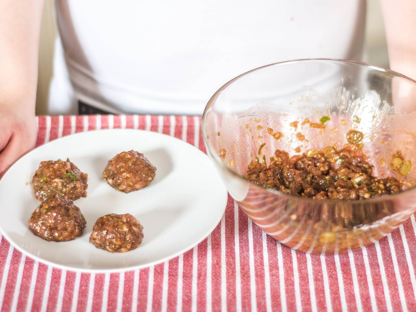 Boil water. Make small meat balls out of the mixture. Here it helps if hands are moistened with water to prevent the balls from sticking. Alternatively, use two teaspoons.