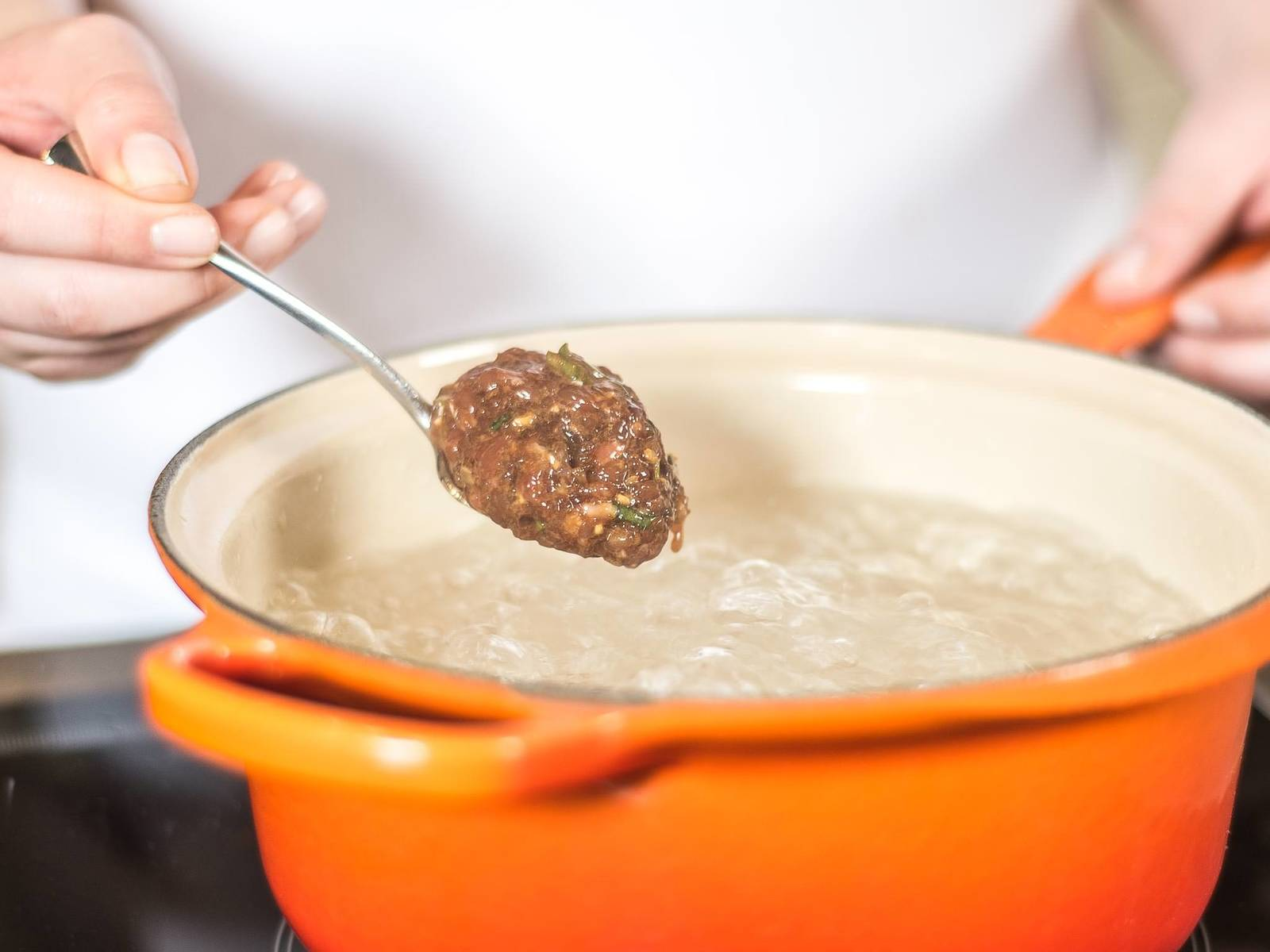 Now, put the meat balls into the boiling water using a spoon.
