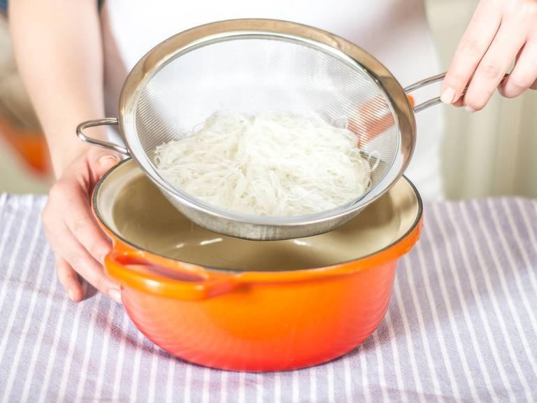 Anschließend Glasnudeln abgießen und unter kaltem Wasser kurz abschrecken. Nach Belieben mit einem Messer kürzen.