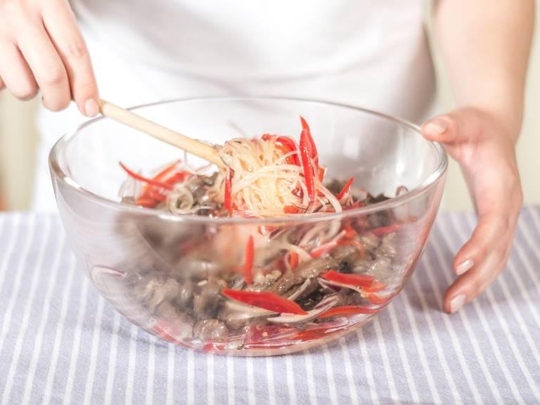 Anschließend die Glasnudeln mit dem Gemüse sowie den Rindfleischstreifen vermengen. Die Erdnüsse unterheben und in einem tiefen Teller serviert lauwarm genießen.