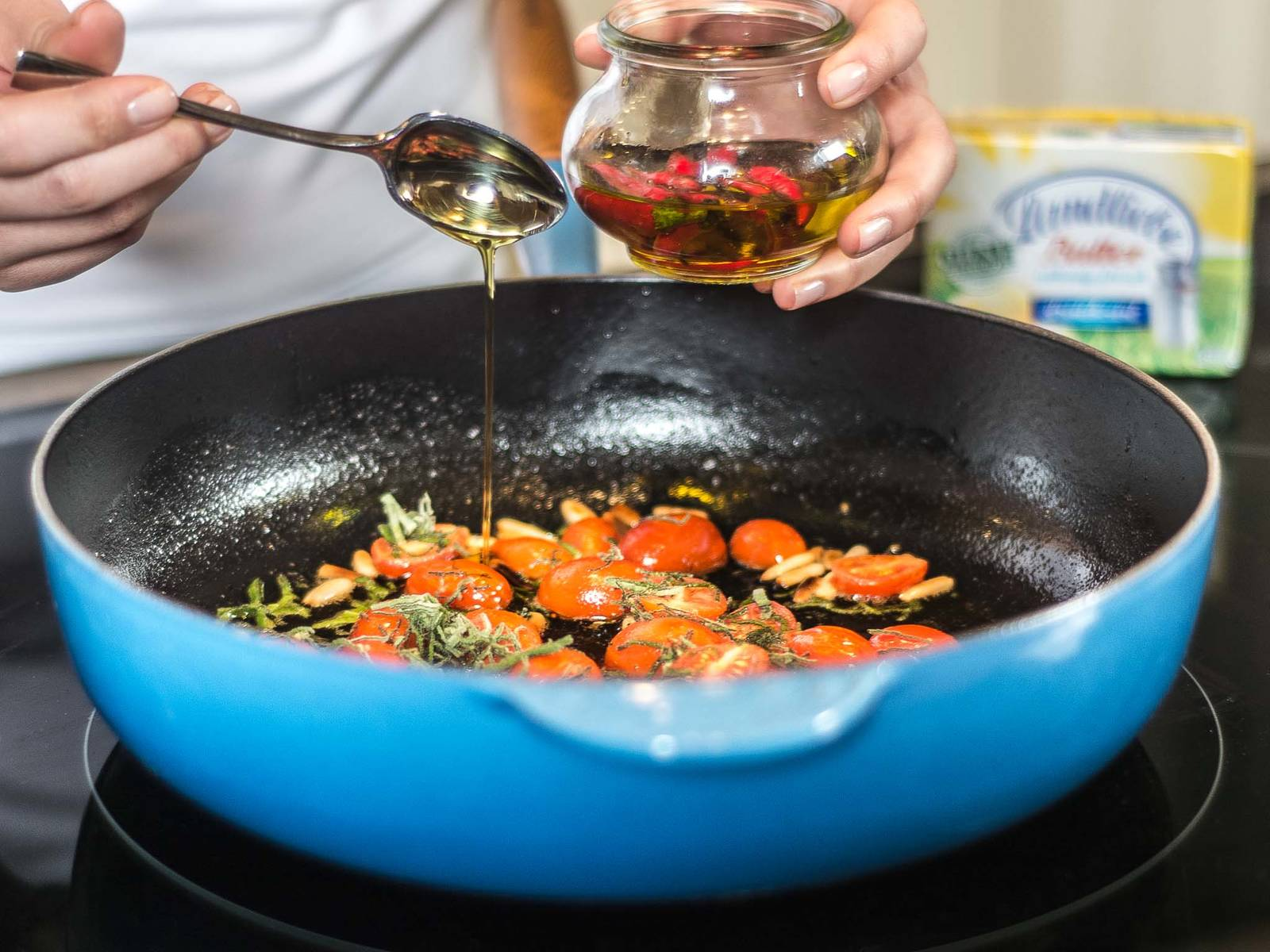 Melt butter in a large frying pan. Add sage, cherry tomatoes, pine nuts, and chili oil and fry. Season lightly with salt and pepper.