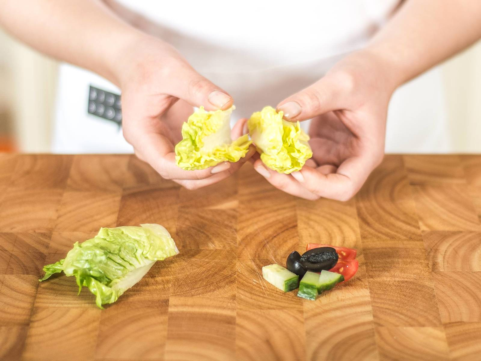 将橄榄与樱桃番茄切半,黄瓜切块。罗马生菜芯洗净,用手撕成块。