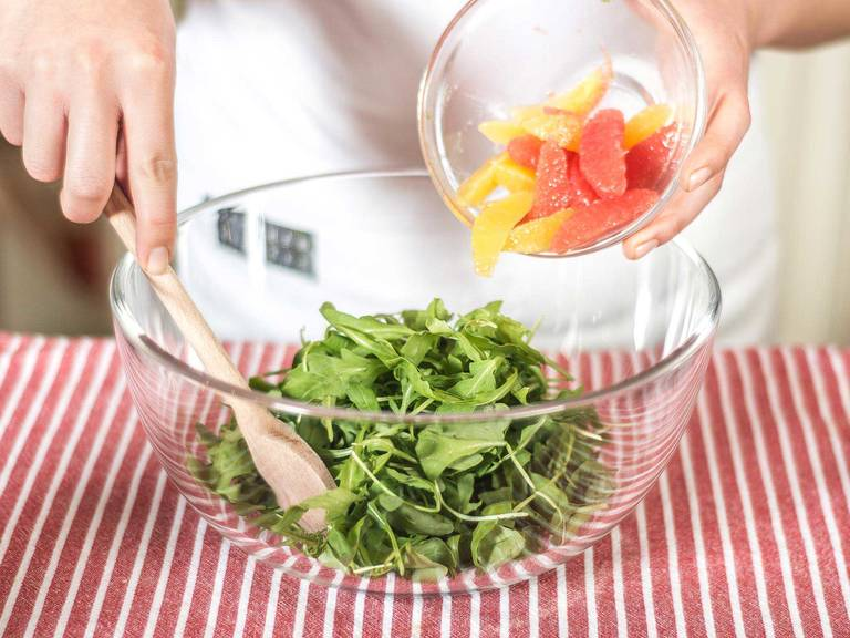 Carefully fold the citrus fillets into the arugula, then mix with the dressing. Once the salad is plated, top with avocado and season with salt and pepper. Serve with a few dollops of pesto.