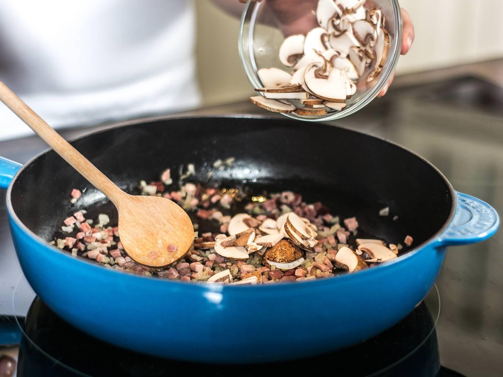 在大平底锅中注入少许植物油,先用高温煸炒培根,然后加入洋葱与蘑菇一起翻炒片刻。
