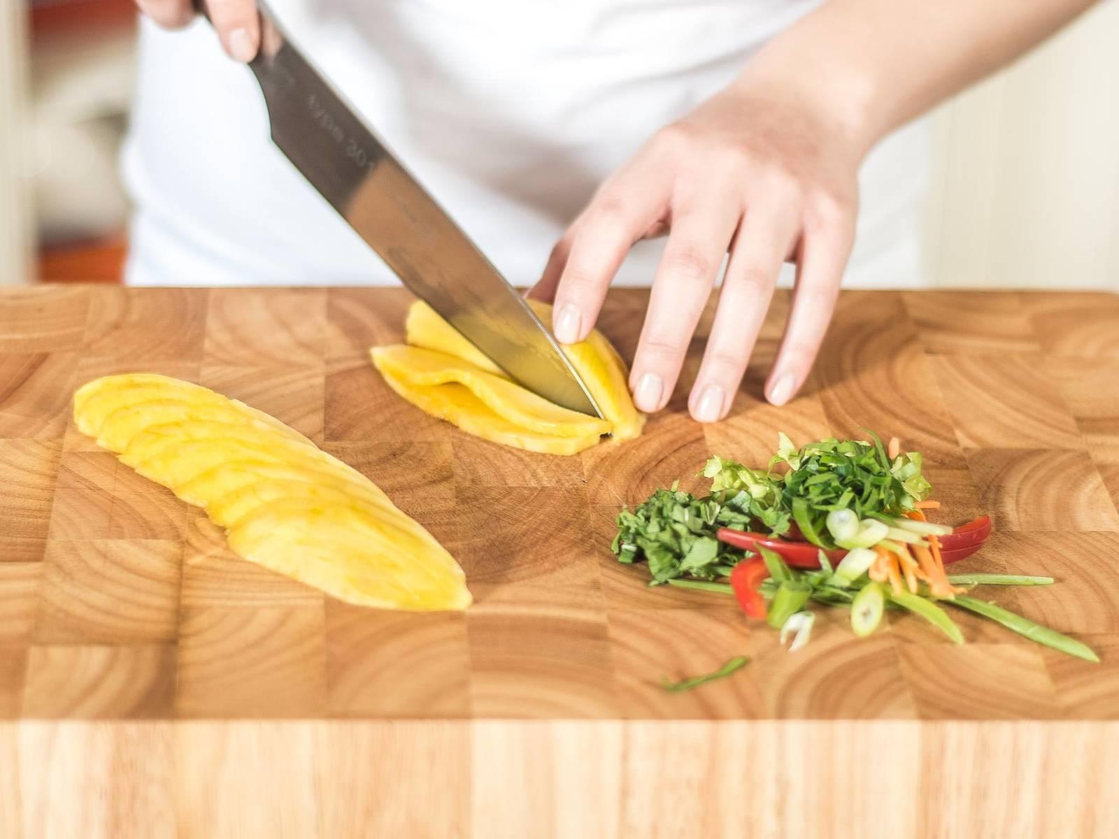 Karotte, Salat, Kaiserschoten, Frühlingszwiebel, Sellerie, Paprika, Minze und Petersilie jeweils in feine Streifen schneiden. Mango schälen, vom Kern befreien und in Scheiben schneiden.