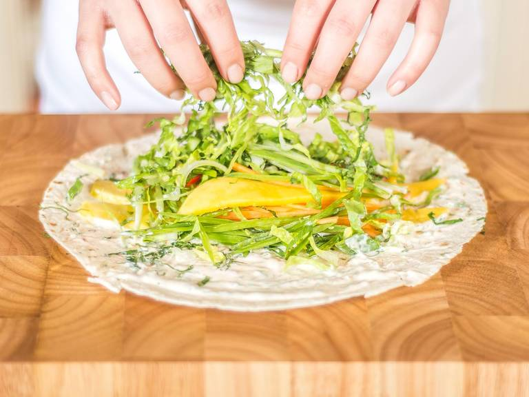 Spread the mixture onto the wraps. Top with sliced vegetables, parsley, and mango.