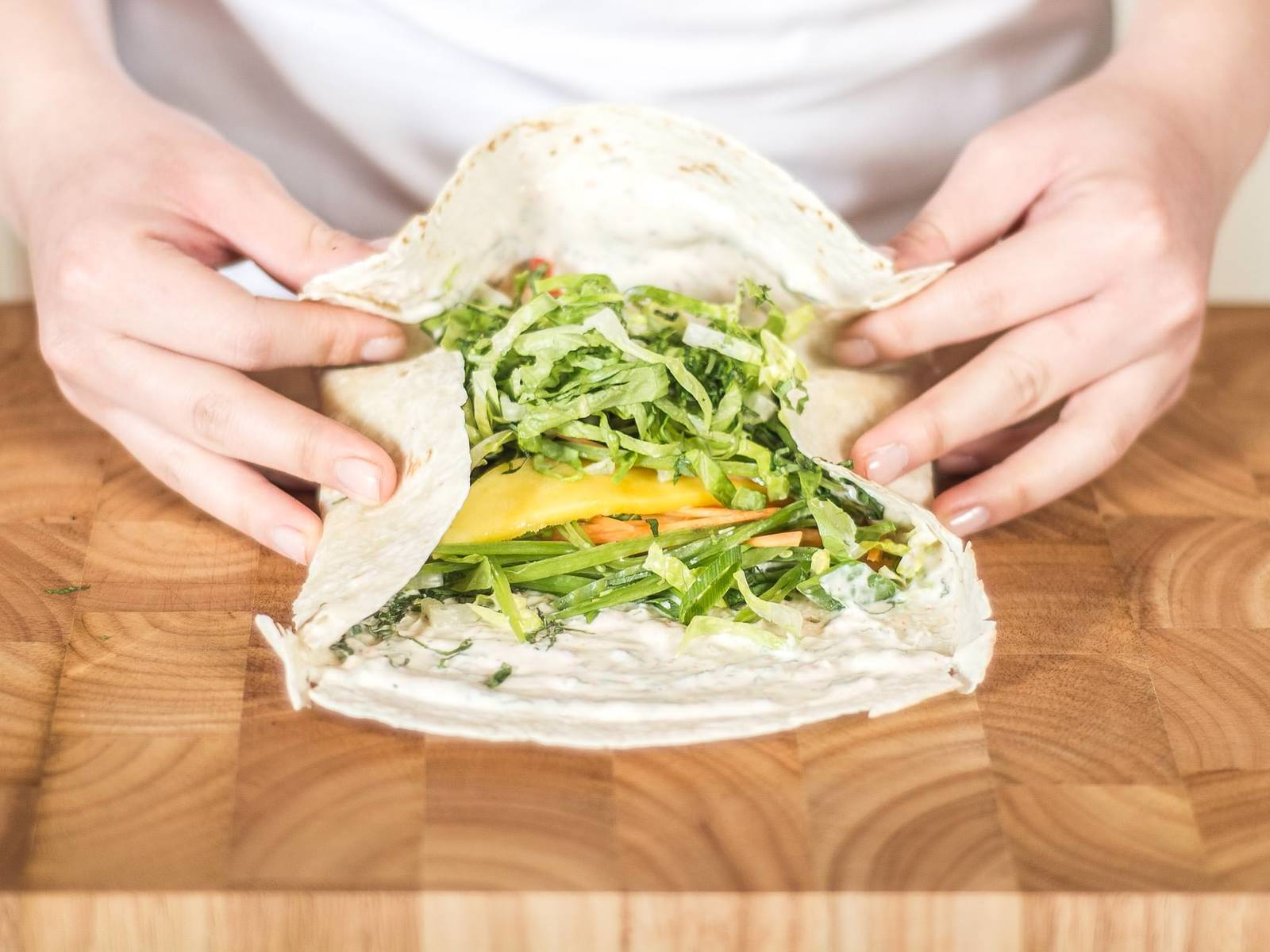 Now, roll to create a wrap. First, fold the edges up and roll as tightly as possible from the widest edge. The less air in the wrap, the easier it is to cut afterwards.