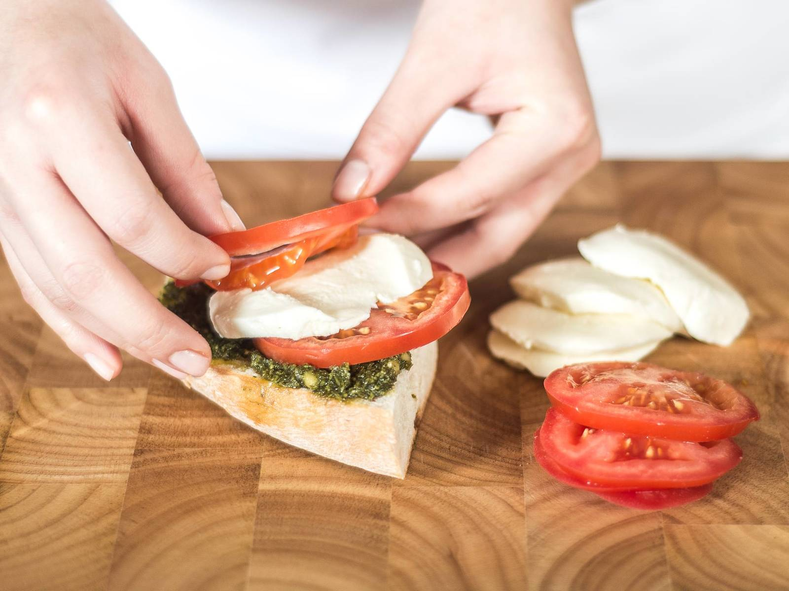 Next, spread the pesto onto the bread and place alternating layers of tomato and mozzarella slices on top.