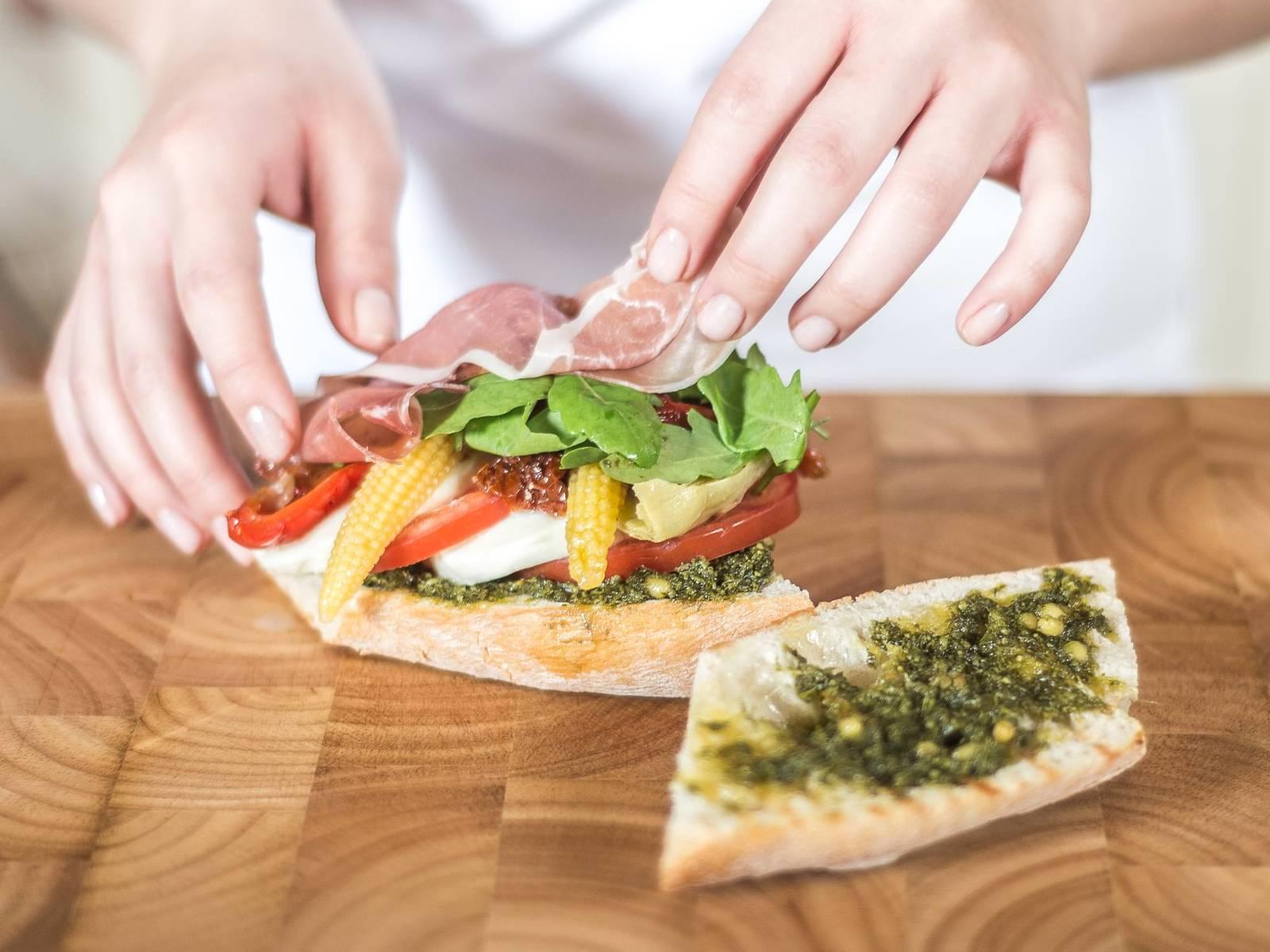再摆上餐前小菜,帕玛火腿及芝麻菜,最后将另一半面包盖上即可。享用时可用木签插入面包以方便食用。