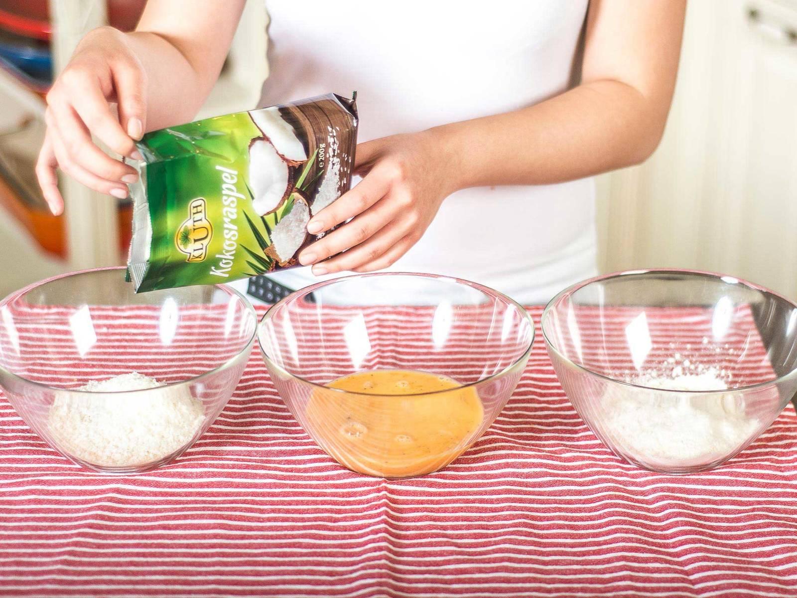 Eine Panierstraße mit drei Schüsseln bilden. In die erste Mehl geben. In der zweiten Eier mit Dijon-Senf und Currypulver verquirlen. In der dritten Panko-Mehl mit Kokosraspeln vermengen.