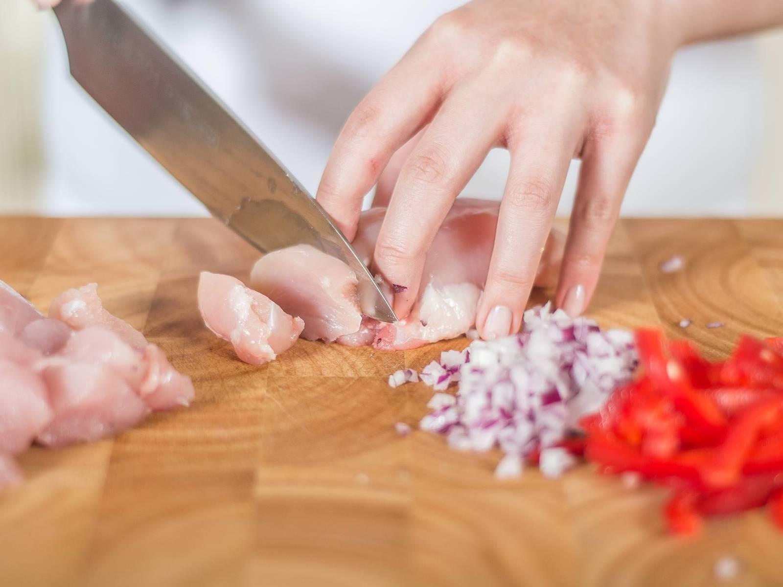 Ingwer hacken, Zwiebel fein würfeln und Paprika in Streifen schneiden. Hähnchenbrust in mundgerechte Würfel schneiden.