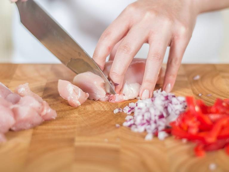 Chop ginger, finely dice onion and slice pepper into strips. Cut chicken breast into small pieces.