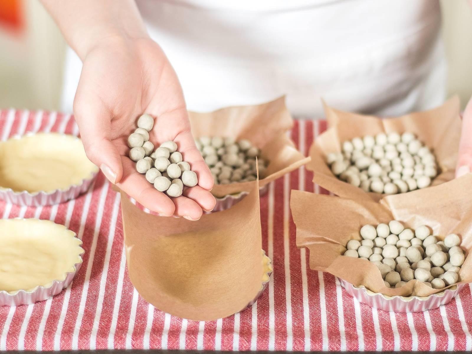 在工作台上撒少许面粉,将面团薄薄地擀开。把面饼分别铺入涂有黄油的8个烤模中,去掉突出的边。铺上烘焙纸,并用干豌豆压住。
