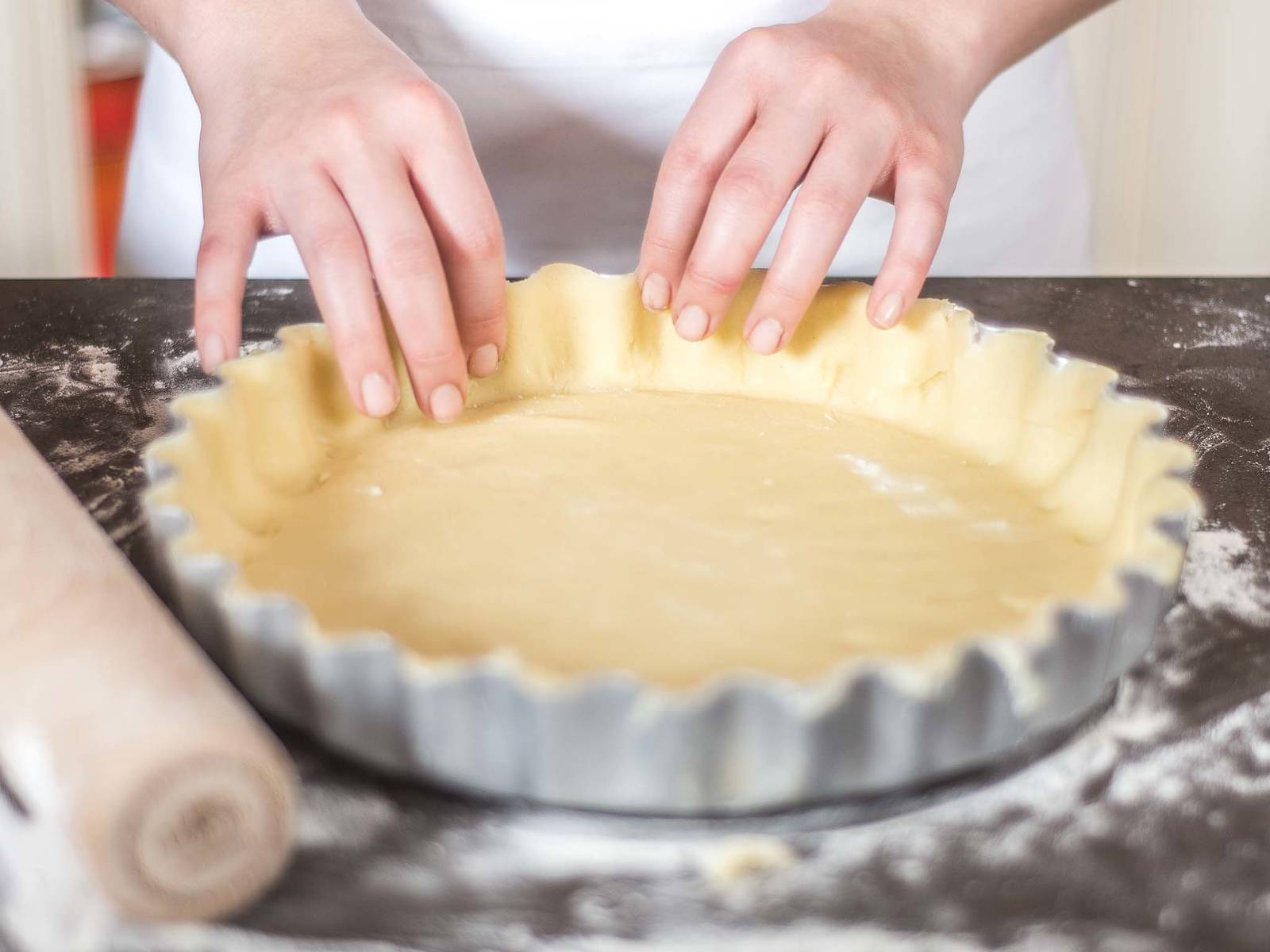 Roll the dough out thinly onto a work surface sprinkled with flour. Leaving an edge, lay into a tart tin (greased if necessary). Weigh down with baking paper and baking beans.