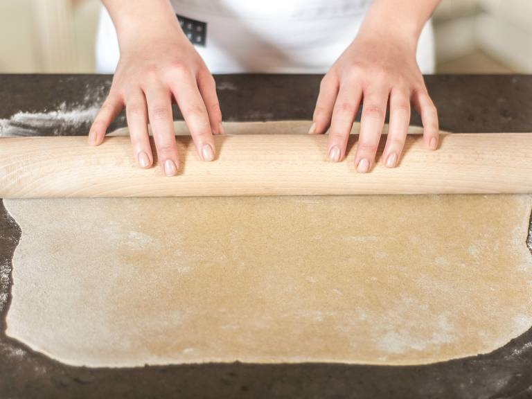 Den Teig in 2 Portionen teilen und auf einer bemehlten Arbeitsfläche zu dünnen Fladen ausrollen. Diese dann auf ein mit Backpapier ausgelegtes Backblech geben.