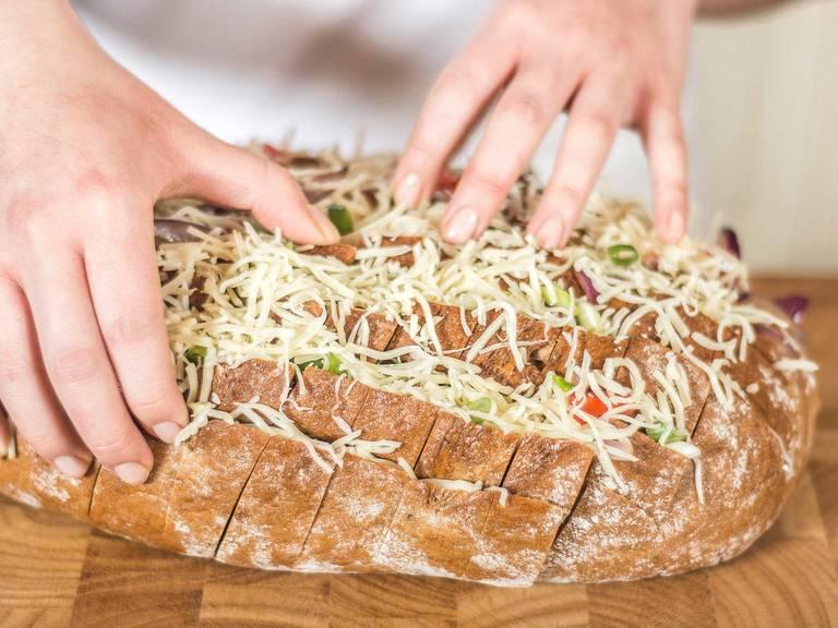 Nun den Brotlaib mit gebratenem Speck und Zwiebeln, Tomatenwürfeln, Frühlingszwiebelringen sowie Käse füllen. Alles möglichst tief in die Spalten drücken.