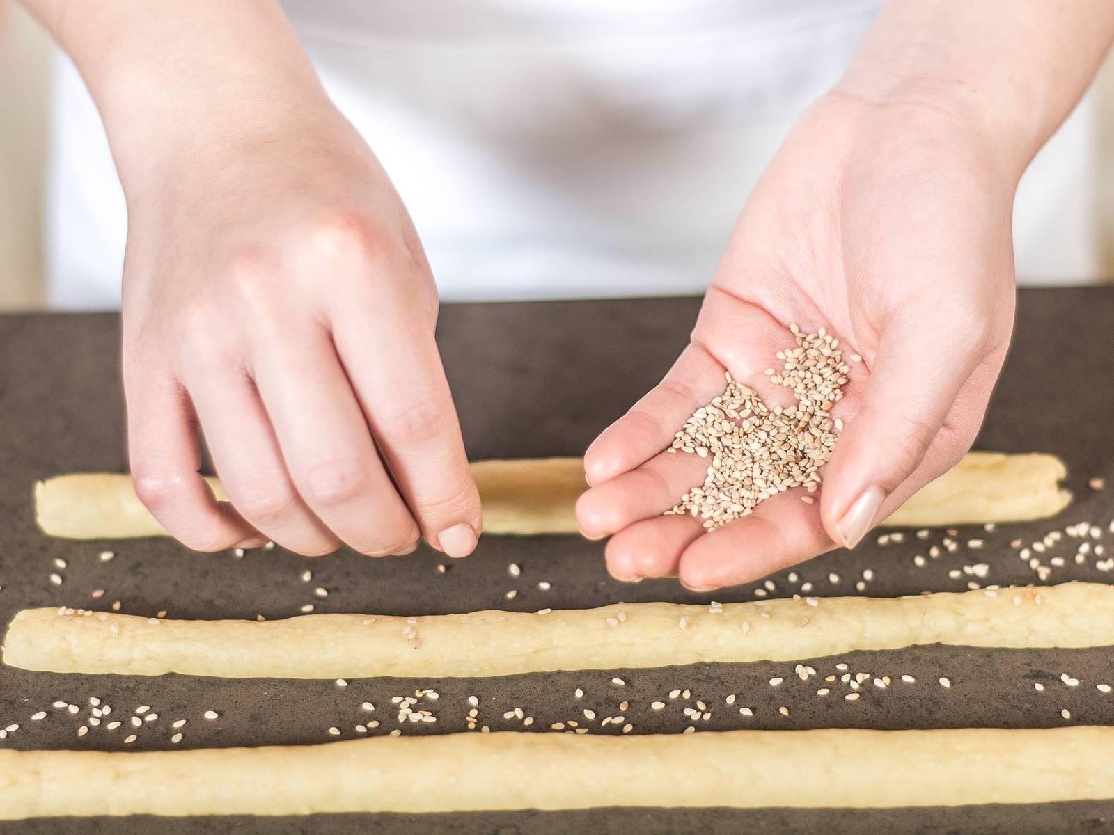 在面包条上撒上芝麻。最好是让面包条在芝麻上滚转,使它们粘得更好。将面包条放入铺有烘焙纸的烤盘中,加盖后放在温暖的地方约20分钟,静置发酵。