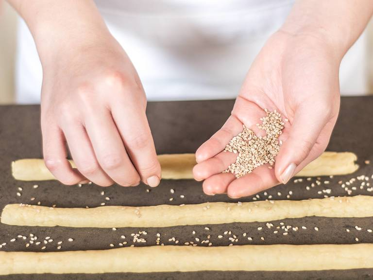 Sprinkle grissini with sesame seeds. Ideally, roll the grissini in the sesame seeds so they stick better. Place the sticks onto a lined baking tray, cover, and leave to rise in a warm place for 20 min.
