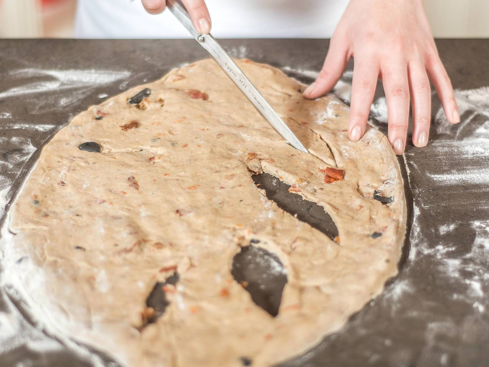Using a sharp knife, cut out individual sections of the dough. Transfer the fougasse onto a baking rack, cover and leave to rise in a warm place for approx. 20 min.