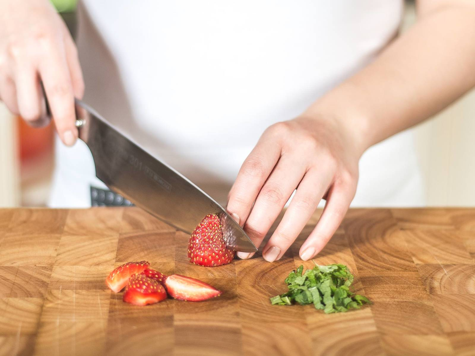 这期间,将薄荷切丝。清洗草莓后去茎,然后切半。