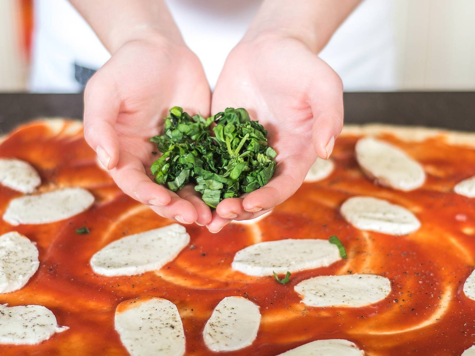 将马苏里拉奶酪片和罗勒丝均匀地铺在番茄蓉上,加盐和胡椒粉调味。