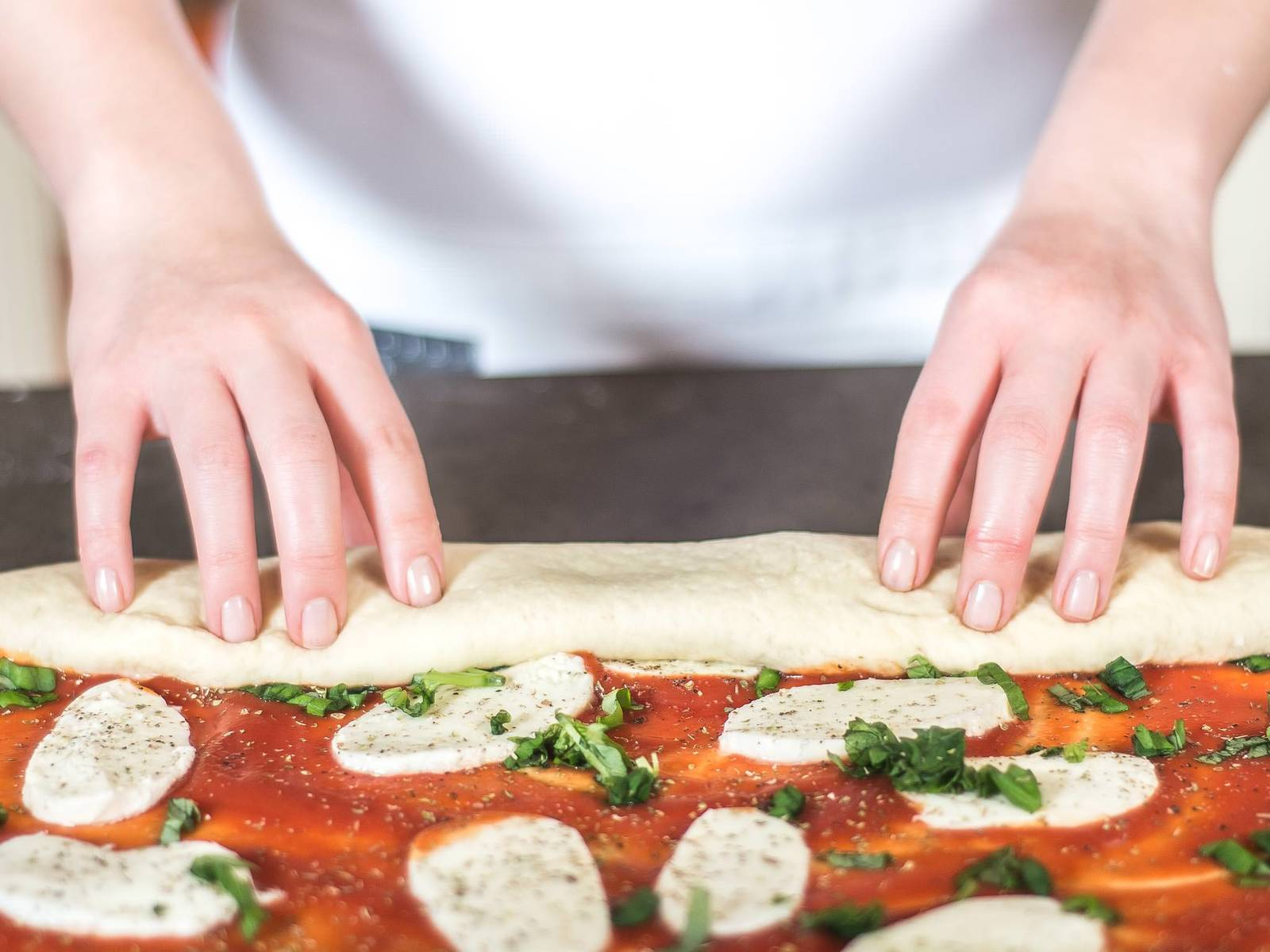 Starting from the long side, roll up the dough from the bottom edge.