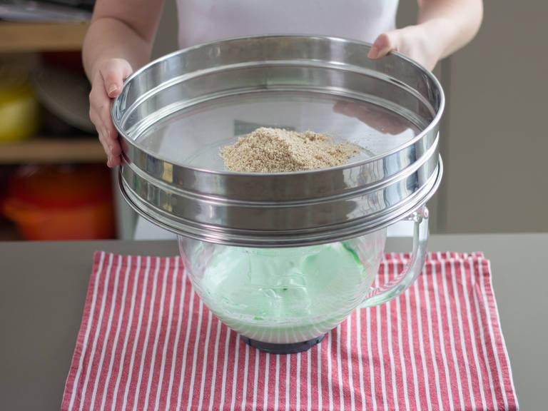 用立式搅拌机搅打蛋白,直至蛋液发泡。加入细砂糖和食物色素后,继续搅打至形成硬性发泡(即当你提起搅拌器,随之拉起的蛋液尖峰短而直小,不应当弯曲)。 筛入杏仁粉,轻轻将其与蛋液混合均匀。